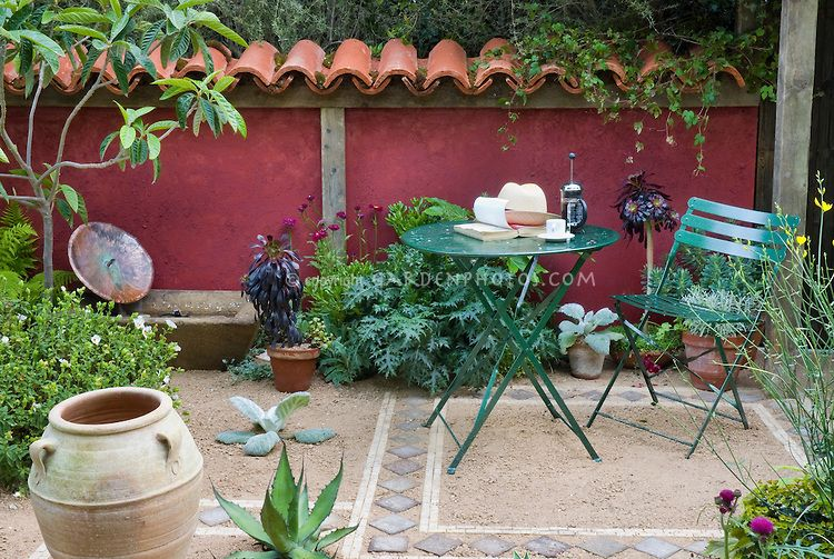 Great Mediterranean Style Garden Courtyard Patio With Terracotta Roof Tile Fence,  Urns, Garden Furniture,