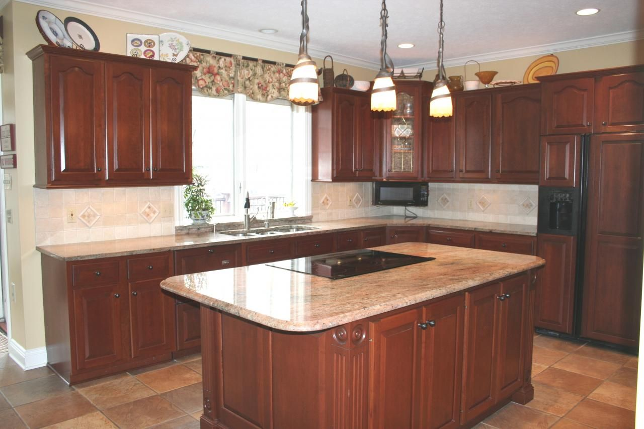 Juparana granite counter top on cherry cabinets lit up by ...