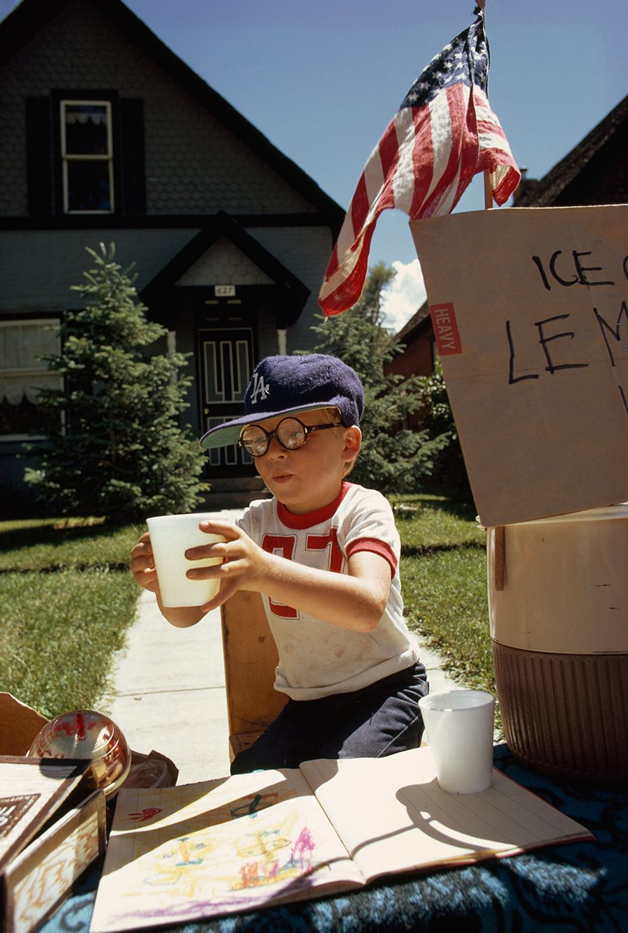 A boy sells lemonade from his front yard stand on Main Street in Aspen, Colorado, 1973.Photograph by Dick Durrance II, National Geographic Creative