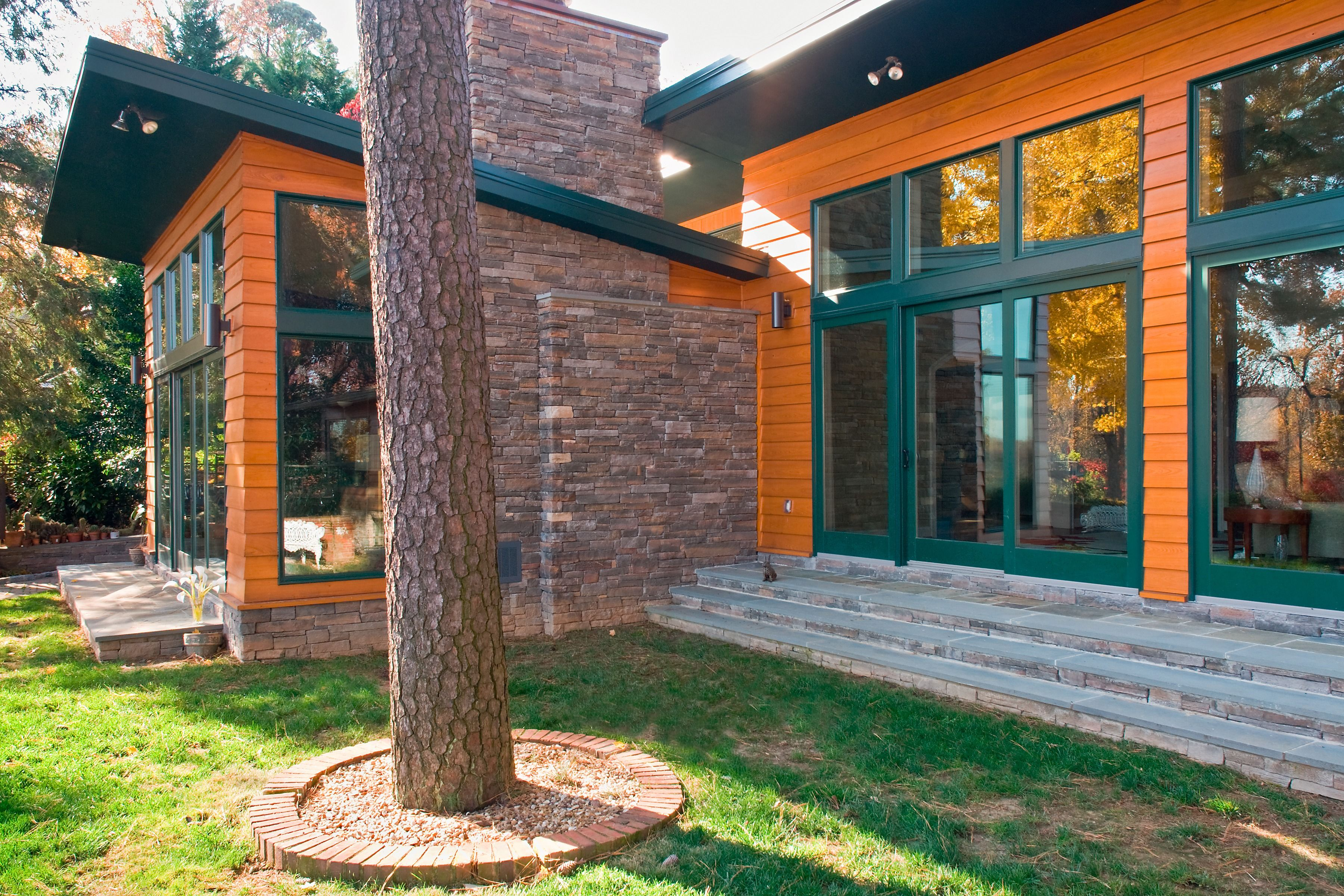 Exterior Featuring Stained Cedar Siding, Stone Chimney, Large Windows, And  Hunter Green Trim