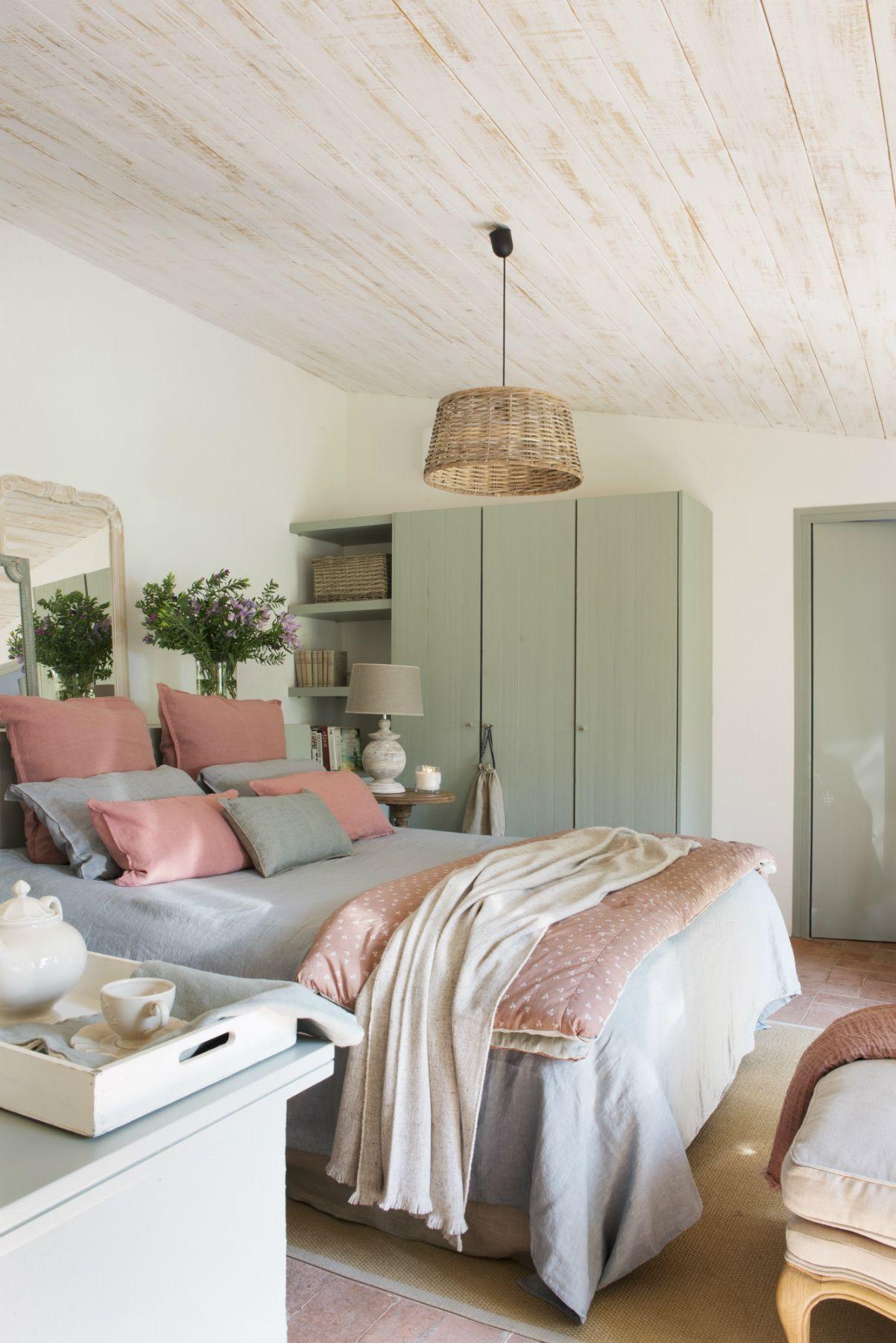 Dormitorio rústico con armario pintado en color verde y ropa de