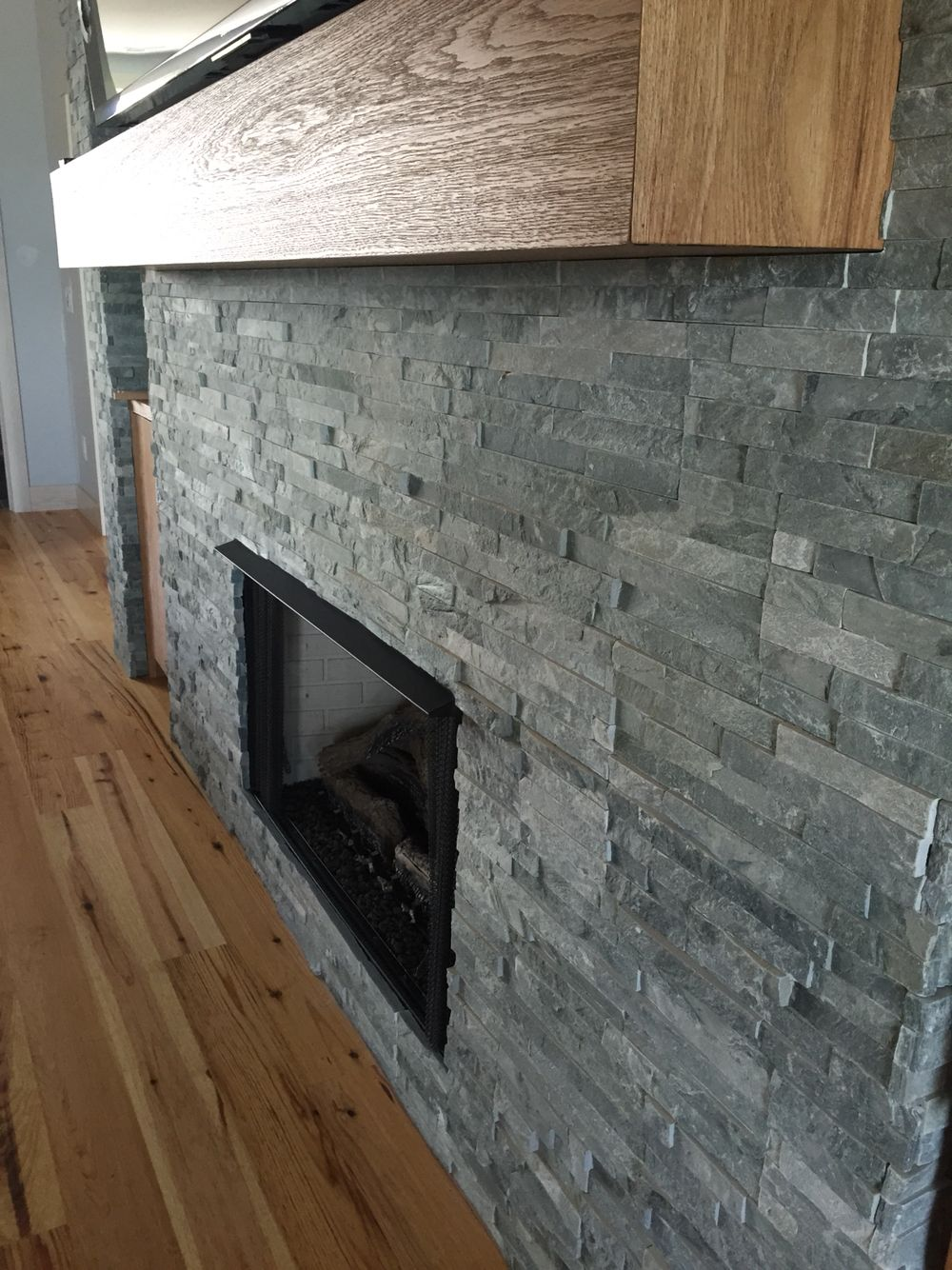 blue stone accent on the fireplace wall surround with a hickory mantle