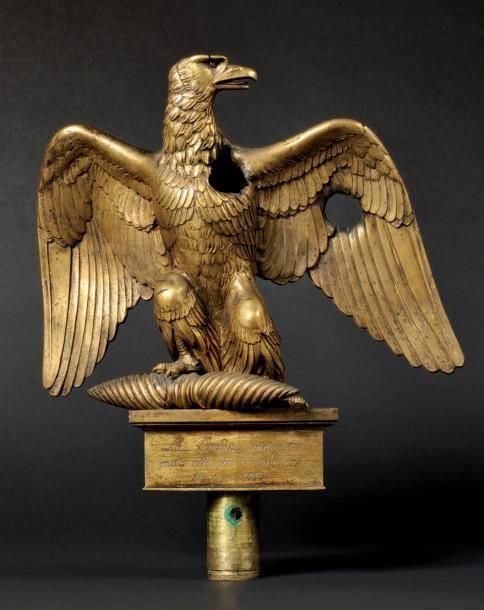 Emouvante aigle de drapeau blessée, modèle 1804. Aigle en bronze doré, à tête tournée vers la gauche, à bec légèrement ouvert, et aux ailes déployées. La patte droite reposant sur le fuseau maintenu par… - Osenat - 15/11/2014