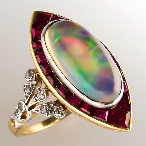 antique Tiffany & Co ring in platinum and 18k yellow gold with 2.35ct oval cabochon opal with .20cts square cut rubies and .80cts old european cut diamonds