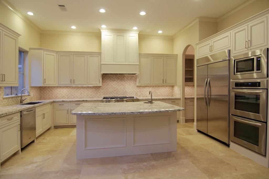 Example of light countertops cabinets and travertine for Kitchen floor tile white cabinets