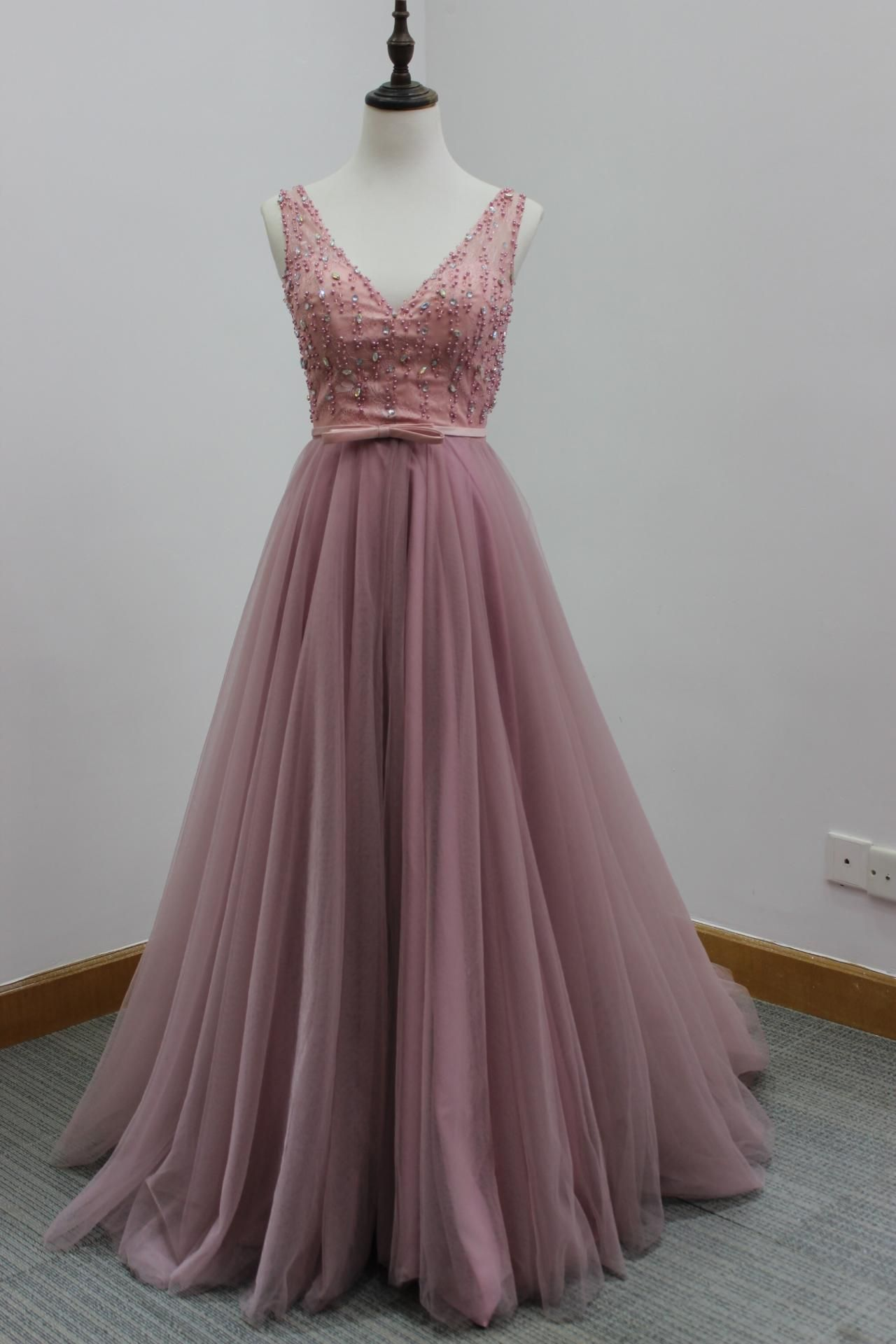 Pink floor length tulle formal gown featuring sleeveless plunge v