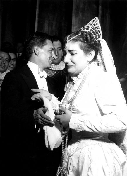 An (almost) unseen photo from the archives at Teatro alla Scala which shows an emotional Maria Callas moved to tears by the incredible success of her Lucia di Lammermoor as the curtain closes mid-performance. A young Herbert von Karajan looks pleased too.