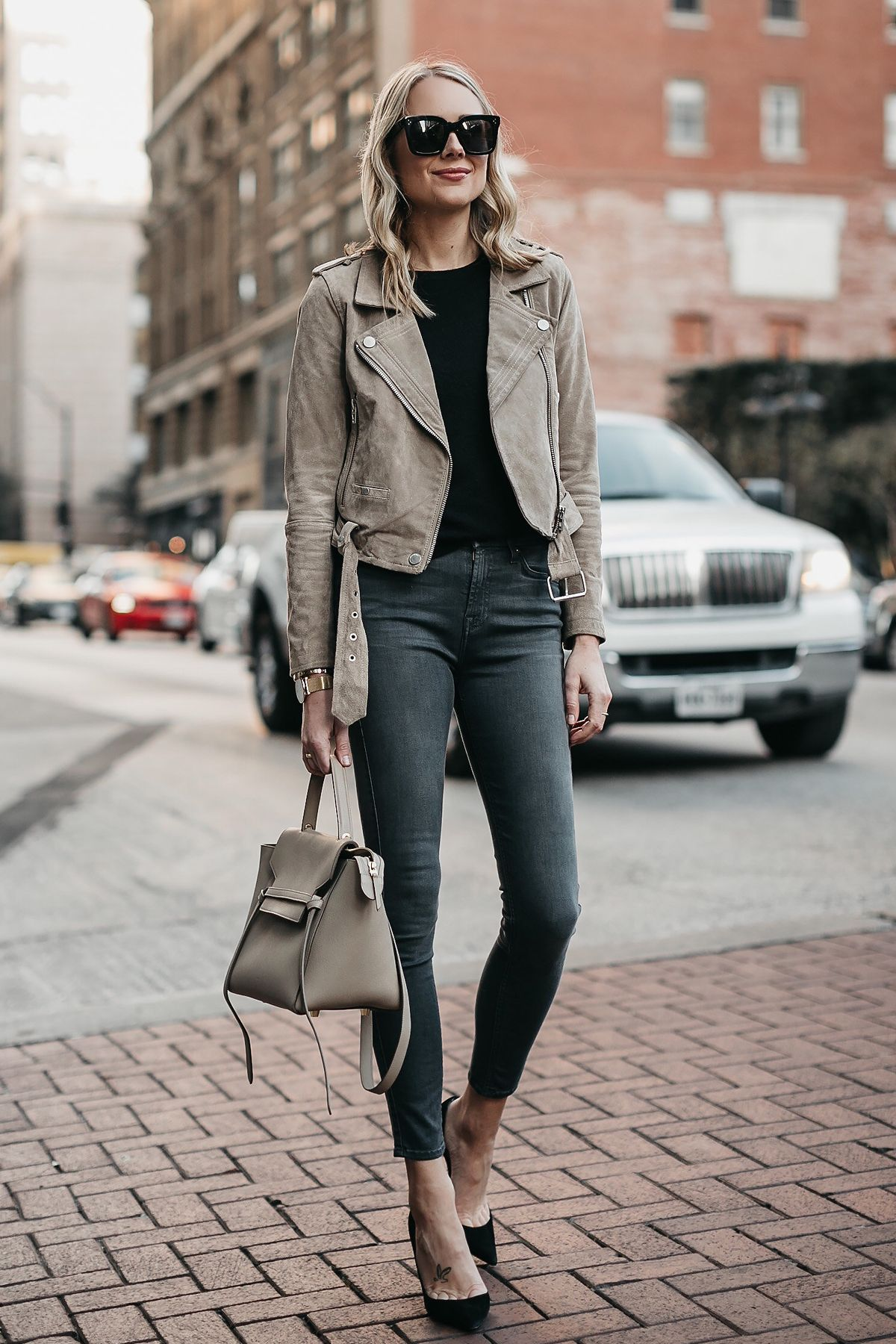 66fd22fcaf Blonde Woman Wearing Blanknyc Suede Moto Jacket Black Sweater 7 For All  Mankind Grey Skinny Jeans Celine Mini Belt Bag Christian Louboutin Black  Pumps ...