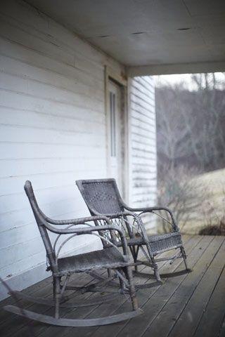 Later oude veranda met barbecue en alleen twee oude schommelstoelen