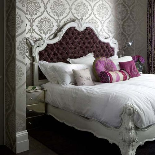 Silver Damask Wallpaper White Mop Board An Ornate Bedframe With Tufted Upholstered Purple Headboard Lots Of Pillows On The Bed