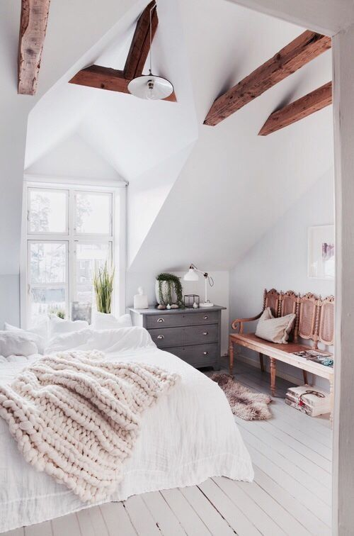 We LOVE the naked wooden beams framing this scandi-inspired bedroom!
