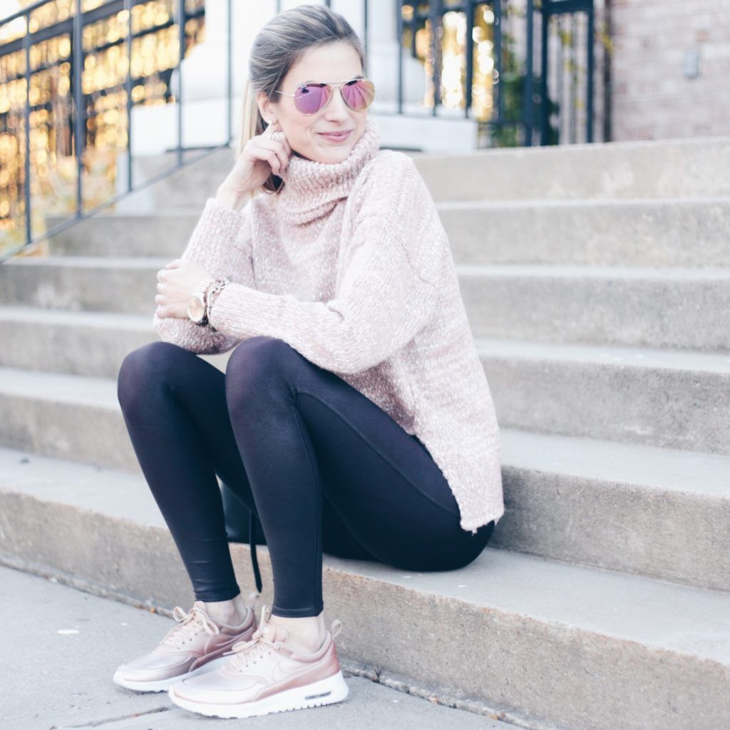 athleisure outfit: pink turtleneck sweater over wine colored spanx leggings  and rose gold nike sneakers