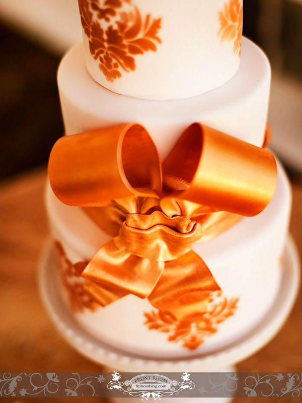 Close up of a three tier white cake with orange ribbon and details. @Sara Dahmen Anniversary wedding. Cake by: Cake Lady.