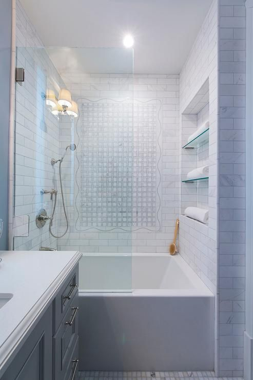 Behind a glass partition, a drop in tub is positioned beneath tiled ...