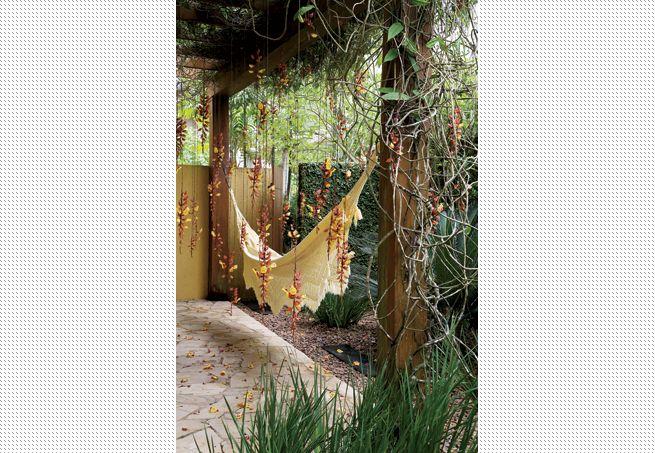 Melhor ainda é passar momentos a dois na rede. Aqui, os cachos de flores pendentes passam a impressão de chuva no jardim. Paisagismo de Irene Cisneros  Evelyn Müller / Casa e Jardim