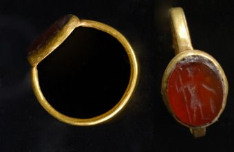 Gold Roman Ring   Thin gold band around an oval bezel with a dark carnelian stone intaglio of Mars holding a spear  2nd to 3rd Century AD