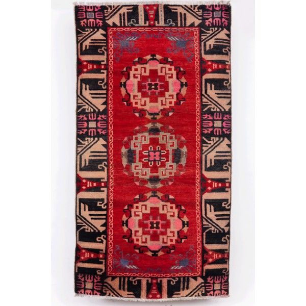 This traditional Tibetan hand-knotted carpet features three medallions against a red field. The outstanding feature is a wide border with a procession of  bird figures, which may be swans or peacocks.