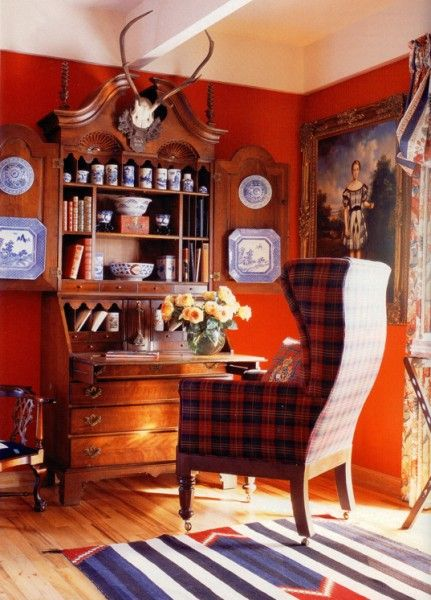 Red walls, blue and white display, antlers, plaid wing-back chair