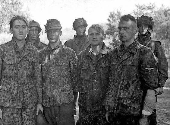 """A group of very young soldiers of the 12th Panzer Division """"Hitlerjugend"""" Waffen SS prisoners in Normandy in July 1944."""