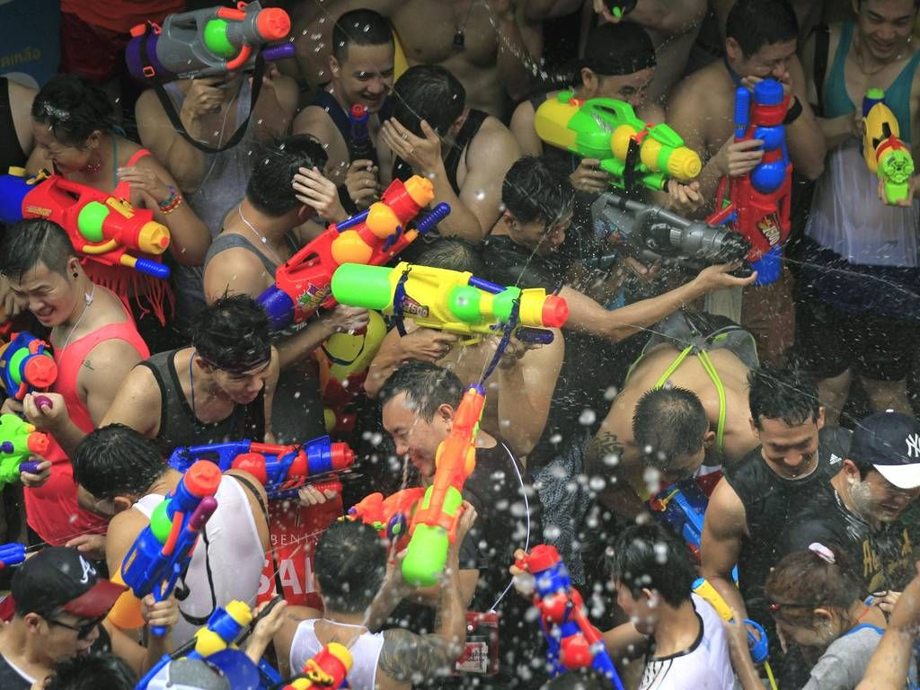 Thai and tourists splash with water as they join the
