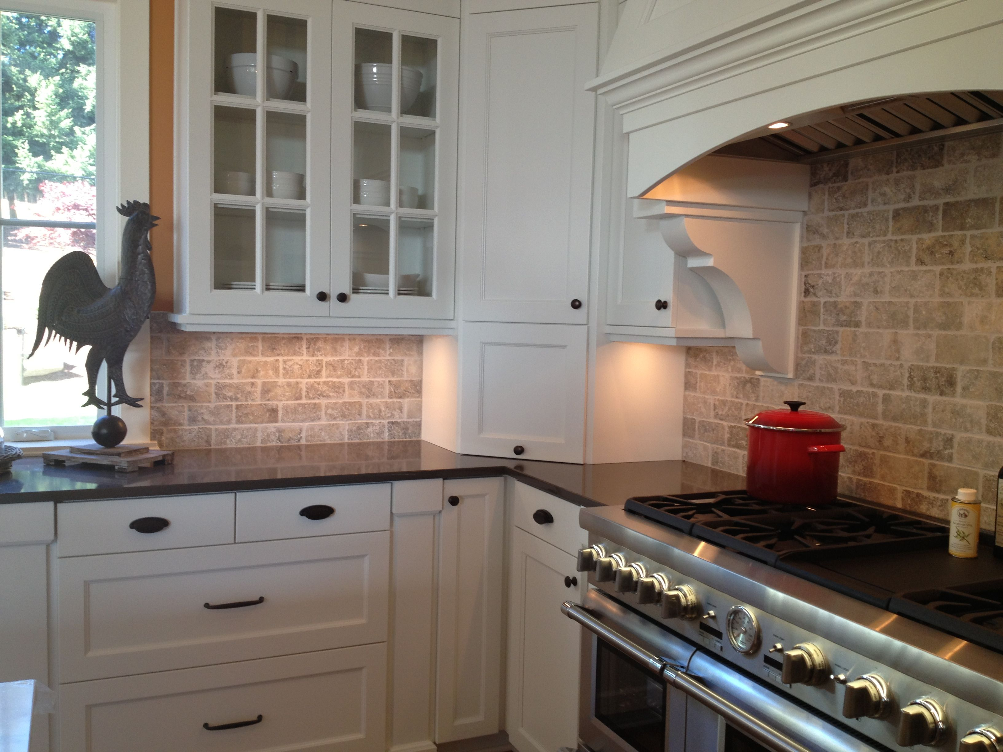 Picture Of Kitchen Travertine Backsplash With White Cabinets And Black Countertop