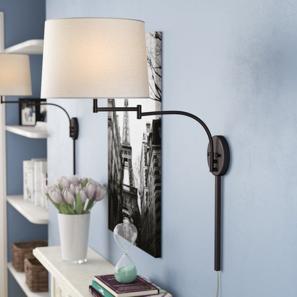 Bring some enhancing illumination to your walls with this one-light swing arm wall sconce. A traditional silhouette, this sconce offers simple, classic-inspired style. Made of steel, this hardwired luminary is perfect as a bedside, office, or den lamp – the extendable arm allows you to move it towards you when needed, and away from you when not in use, saving your table space for books, magazines, coffee mugs, and more. Beneath the white drum shade sits one bulb of up to 100 W (not included).