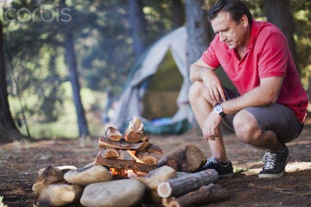Man starting a fire at campsite - 42-29070436 - Libre de derechos - Fotografía de stock: Corbis