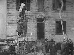 """Life of an American Fireman - Thomas Edison usou pela primeira vez a técnica de edição de imagens. Em seu filme """"Life of an American Fireman"""" de 1903 é possível ver duas imagens diferentes mas que ocorreram simultâneamente, a visão de uma mulher sendo resgatada por um bombeiro e a mesma cena com a visão do bombeiro resgatando a mulher."""
