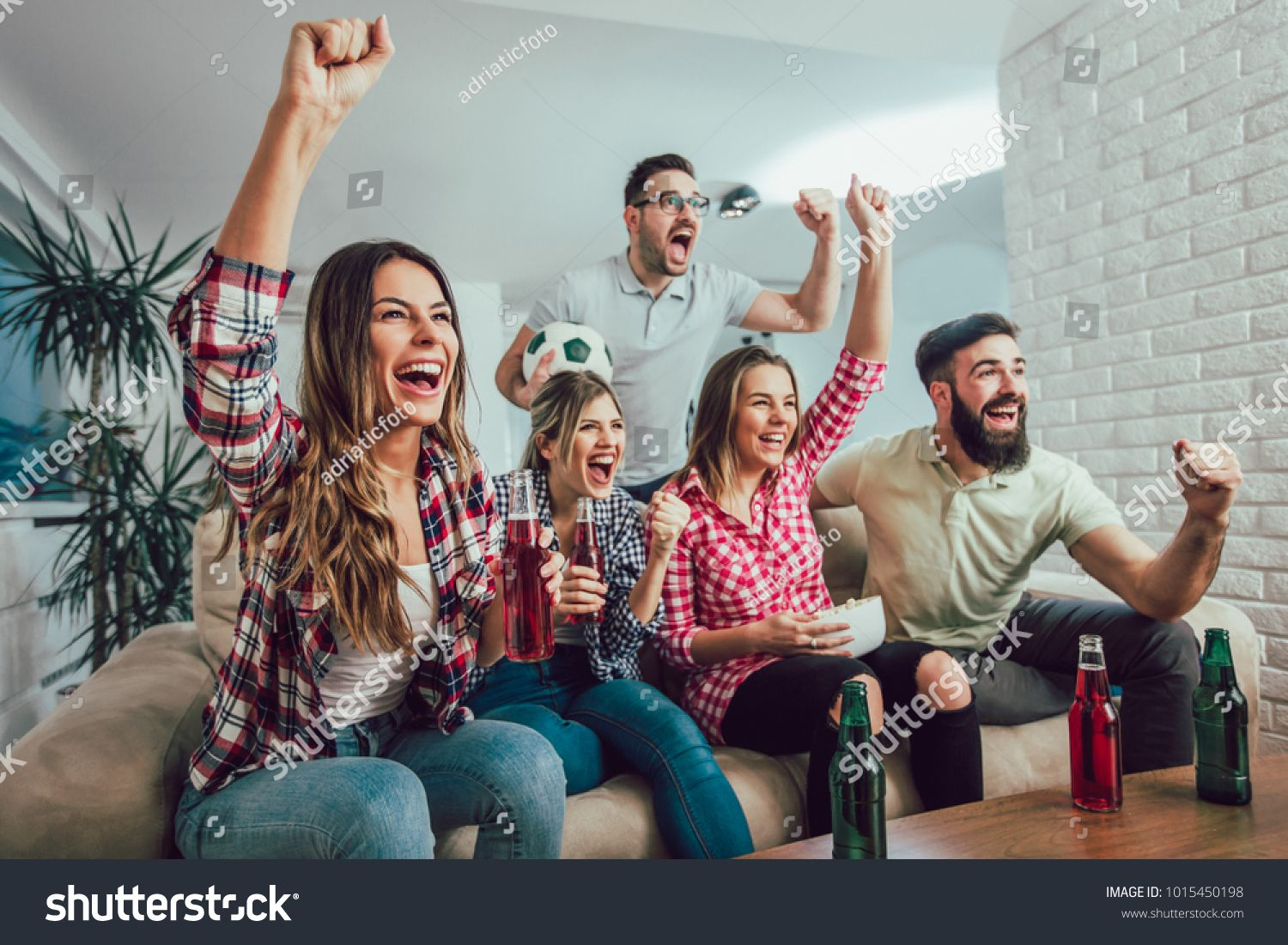 Happy Friends Or Football Fans Watching Soccer On Tv And Celebrating Victory At Home Friendship Sports And Entertainment Concept
