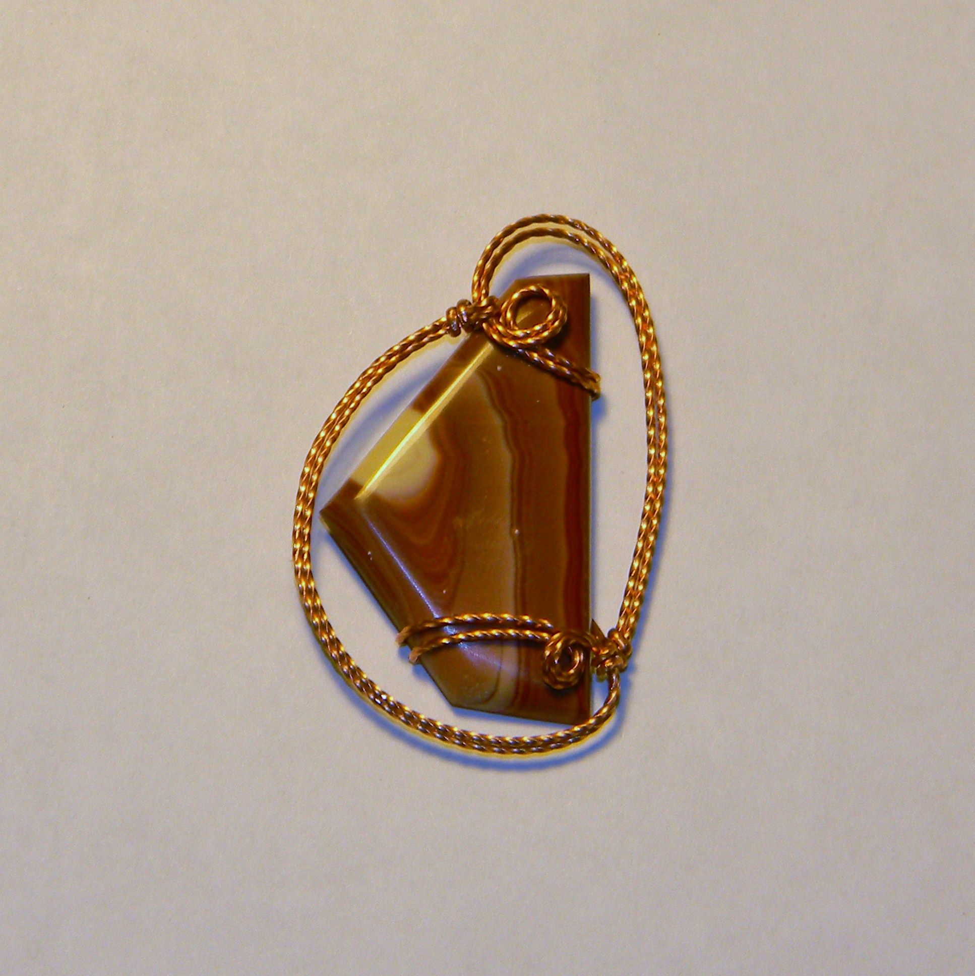"""This is a hickoryite cab wrapped in copper wire. This pendant with an 18"""" leather cord runs $40."""