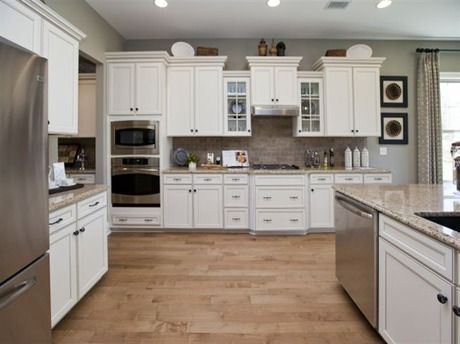 A Timeless White Kitchen With Varied Cabinet Height And A Pair Of