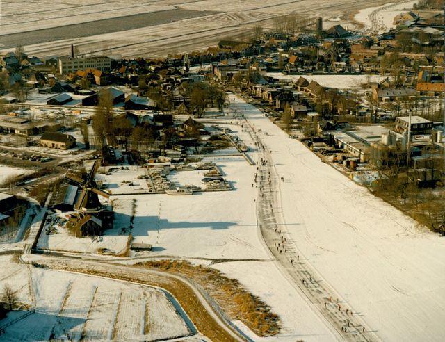 Beeld van de 14e Elfstedentocht. Luchtfoto van een gedeelte van IJlst. Links op de achtergrond de Nooitgedacht fabriek en links op de voorgrond houtzaagmolen De Rat.  26 februari 1986