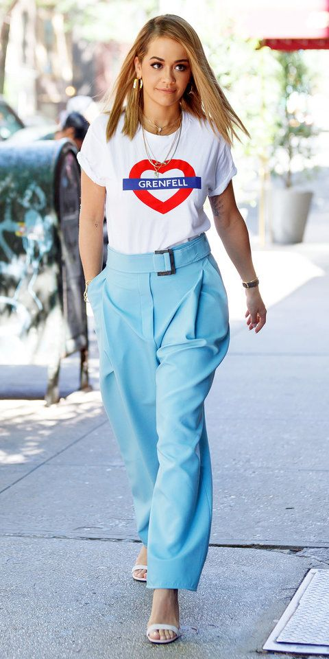 Rita Ora paid tribute to Grenfell Towers victims when she stepped on in London donning a #Love4grenfell t-shirt. She also wore a pair of high rise trousers with a matching wide belt, nude strappy sandals, and layers of gold jewelry.