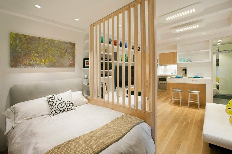 This small apartment has used a simple wooden room divider to separate the bedroom from the rest of the interior.