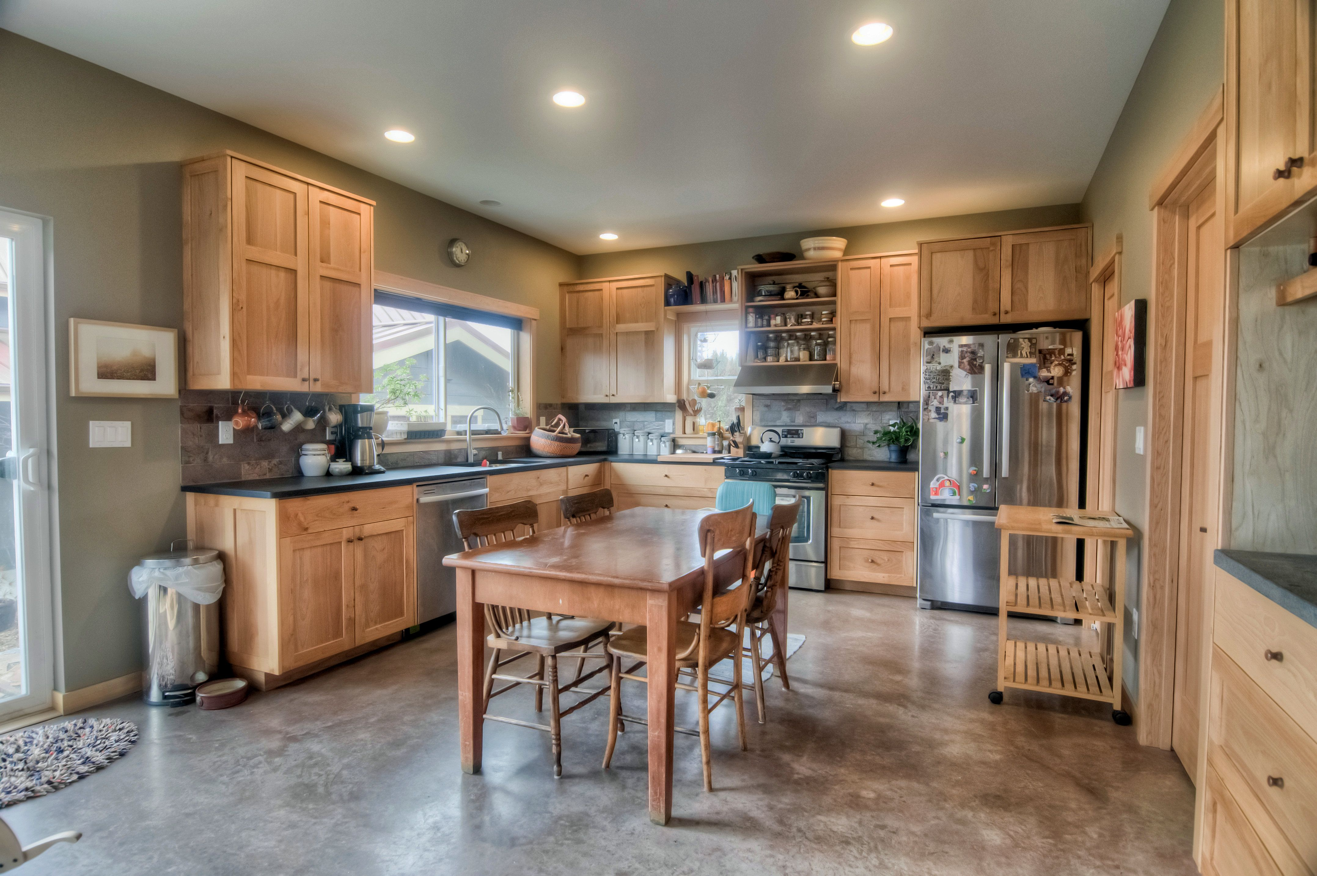 Custom Maple Kitchen Cabinets With Stone Tile Backsplash And Stained Concrete Floors Millw Stained Kitchen Cabinets Contemporary Kitchen Concrete Kitchen Floor