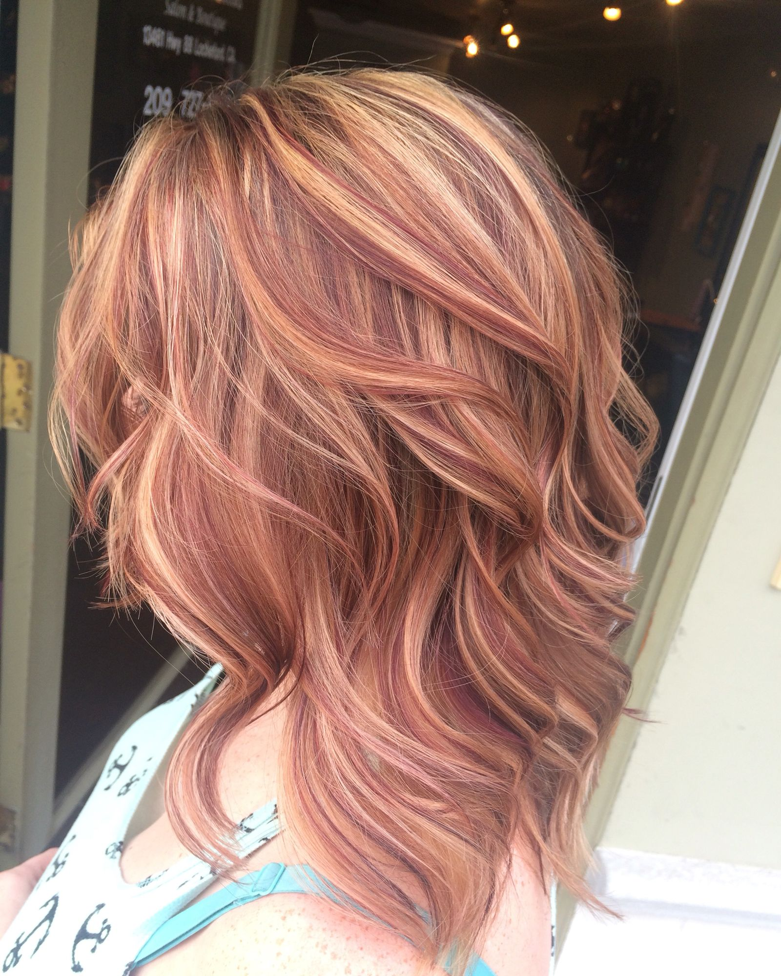 Blonde and red highlights in brown curly hair