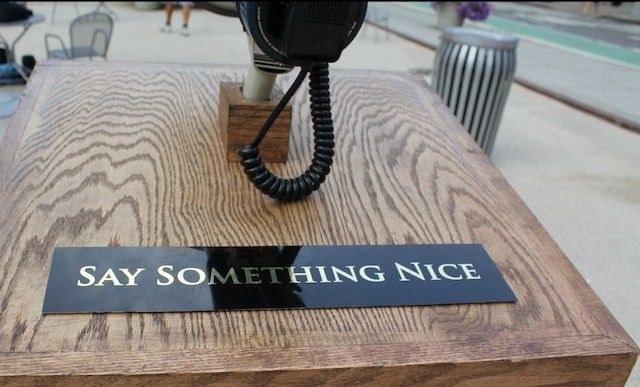 "For their latest project, art collective Improv Everywhere constructed a custom wooden lectern with a megaphone holster and an attached sign that read, ""Say Something Nice."""