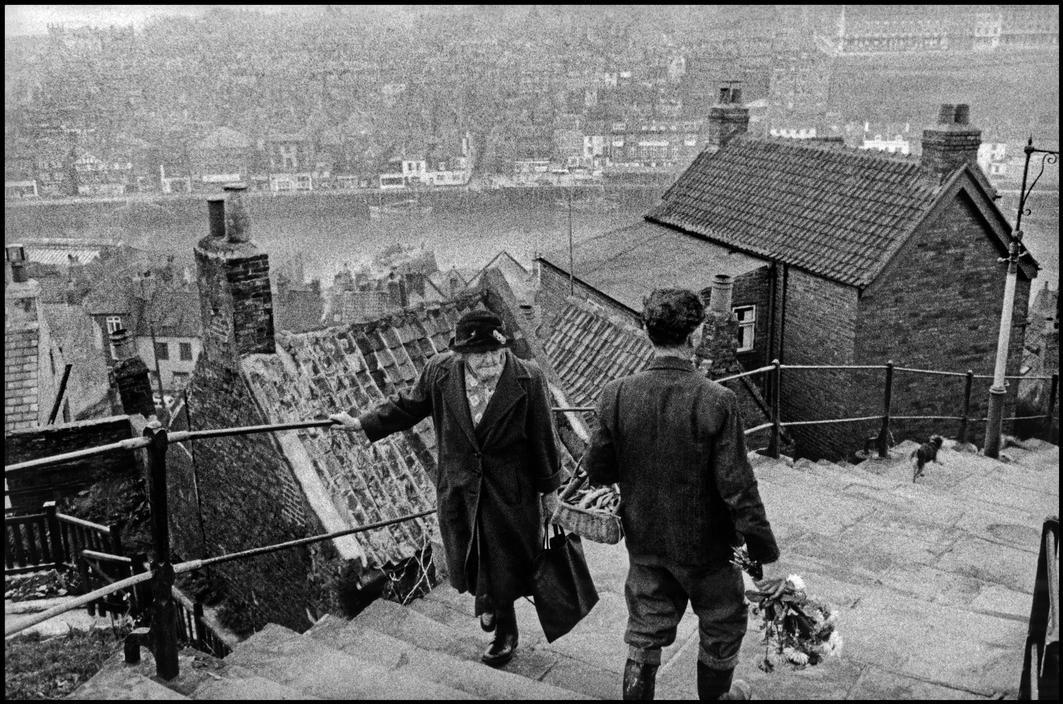 Bruce Davidson, Man carrying flowers passes old woman, England & Scotland portfolio, UK, 1960. © Bruce Davidson/Magnum Photos.