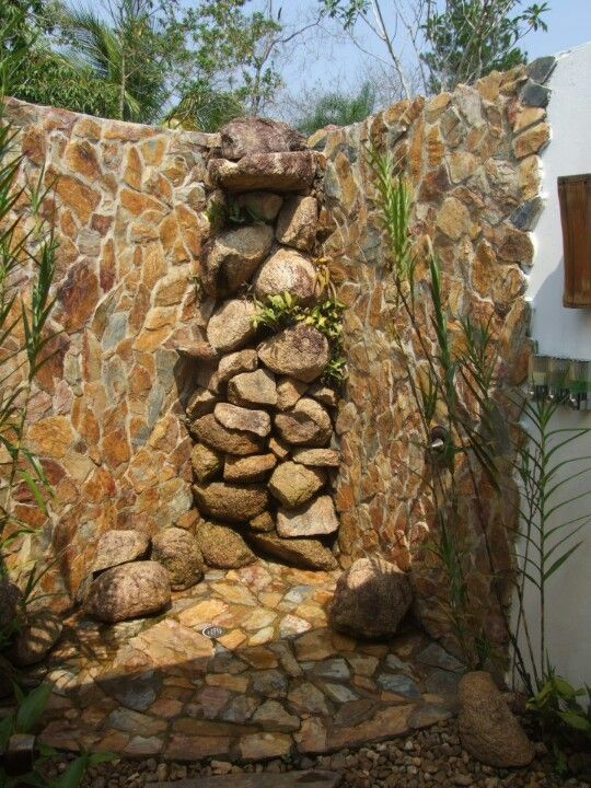 Outdoor shower with natural rock surround and floor base. LOVE this one