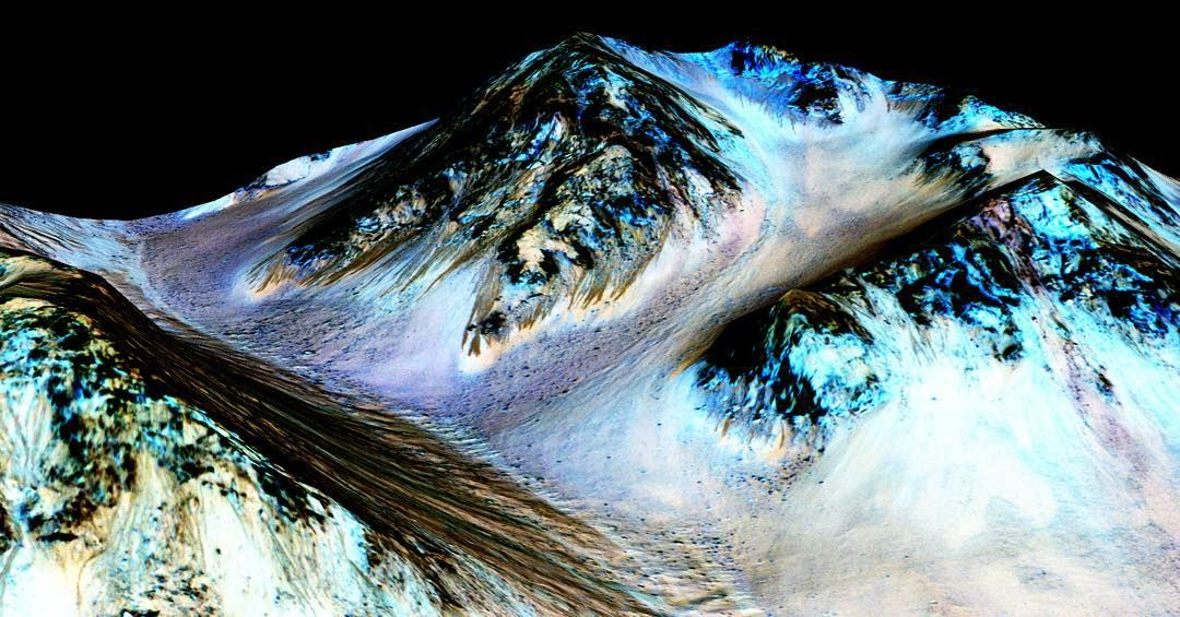 """#icymi Dark narrow streaks on Martian slopes such as these at Hale Crater are inferred to be formed by seasonal flow of water # on contemporary Mars. The streaks are roughly the length of a football field.  The imaging and topographical information in this processed false-color view come from the High Resolution Imaging Science Experiment (HiRISE) camera on NASA's Mars Reconnaissance Orbiter.  These dark features on the slopes are called """"recurring slope lineae"""" or RSL. Planetary scientists…"""