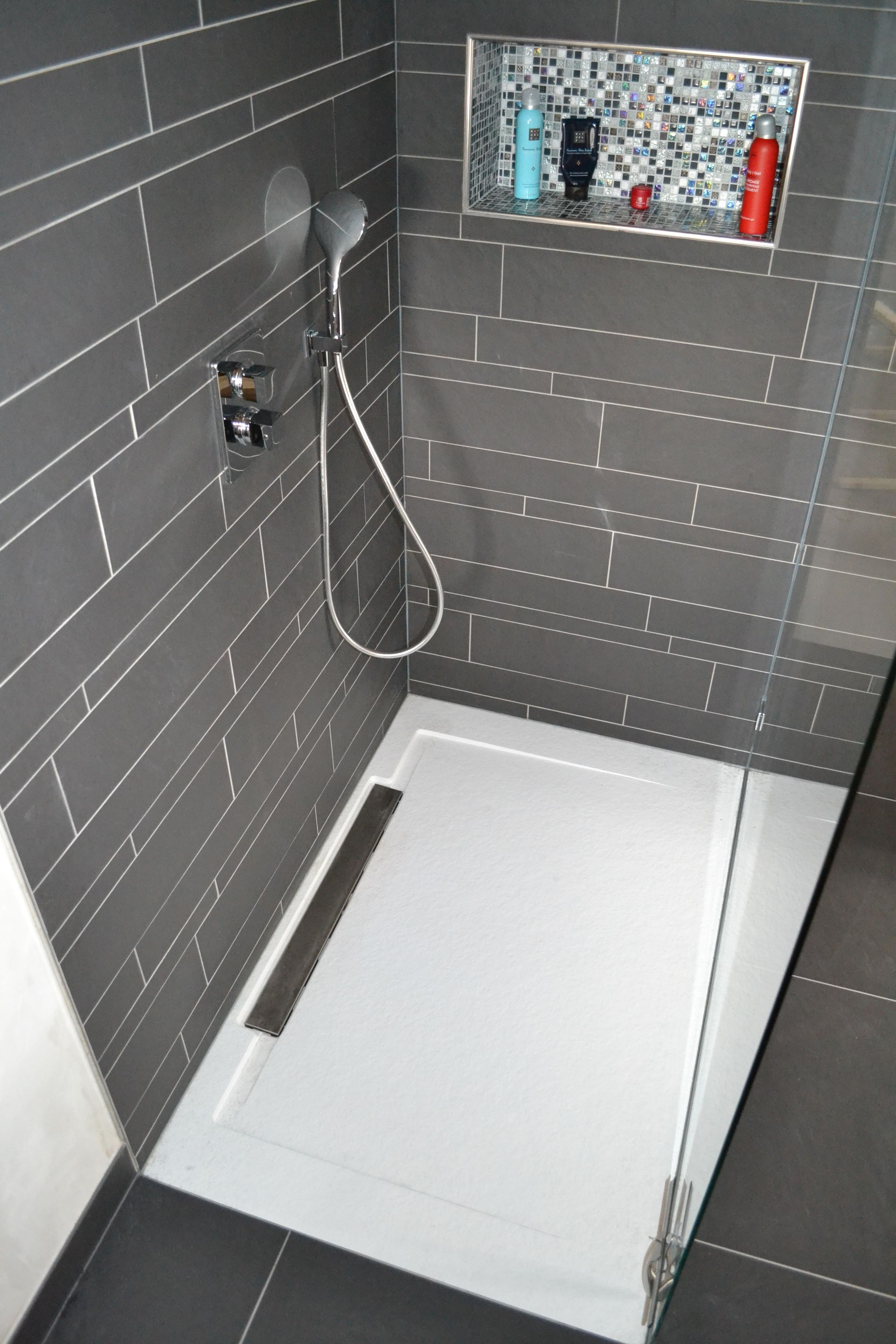Een geïntegreerde douchetegel van Dekker Zevenhuizen. Deze tegel sluit naadloos aan op de vloertegel.