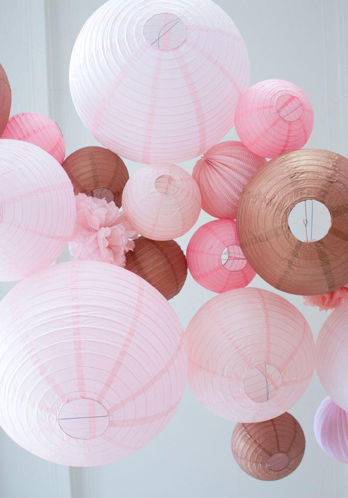 Décoration de mariage rose or avec un ciel de lanternes et de pompons en papier