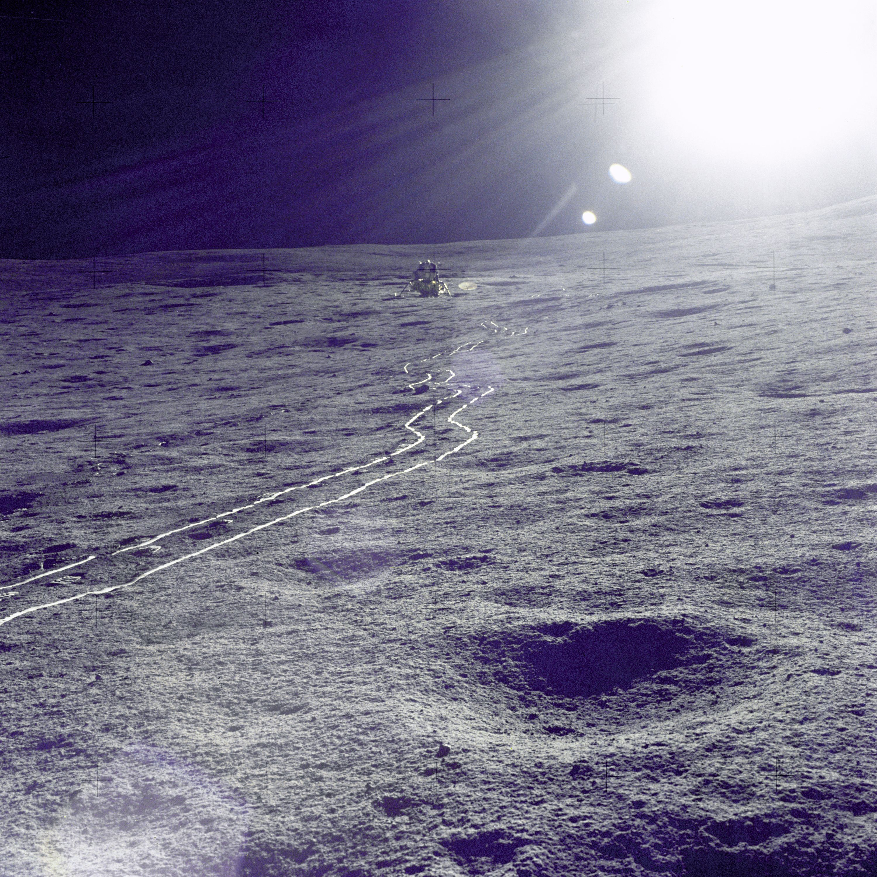 "The Apollo 14 Lunar Module (LM) ""Antares"" is photographed against a brilliant sun glare during the first extravehicular activity (EVA-1). A bright trail left in the lunar soil by the two-wheeled Modularized Equipment Transporter (MET) leads from the LM."