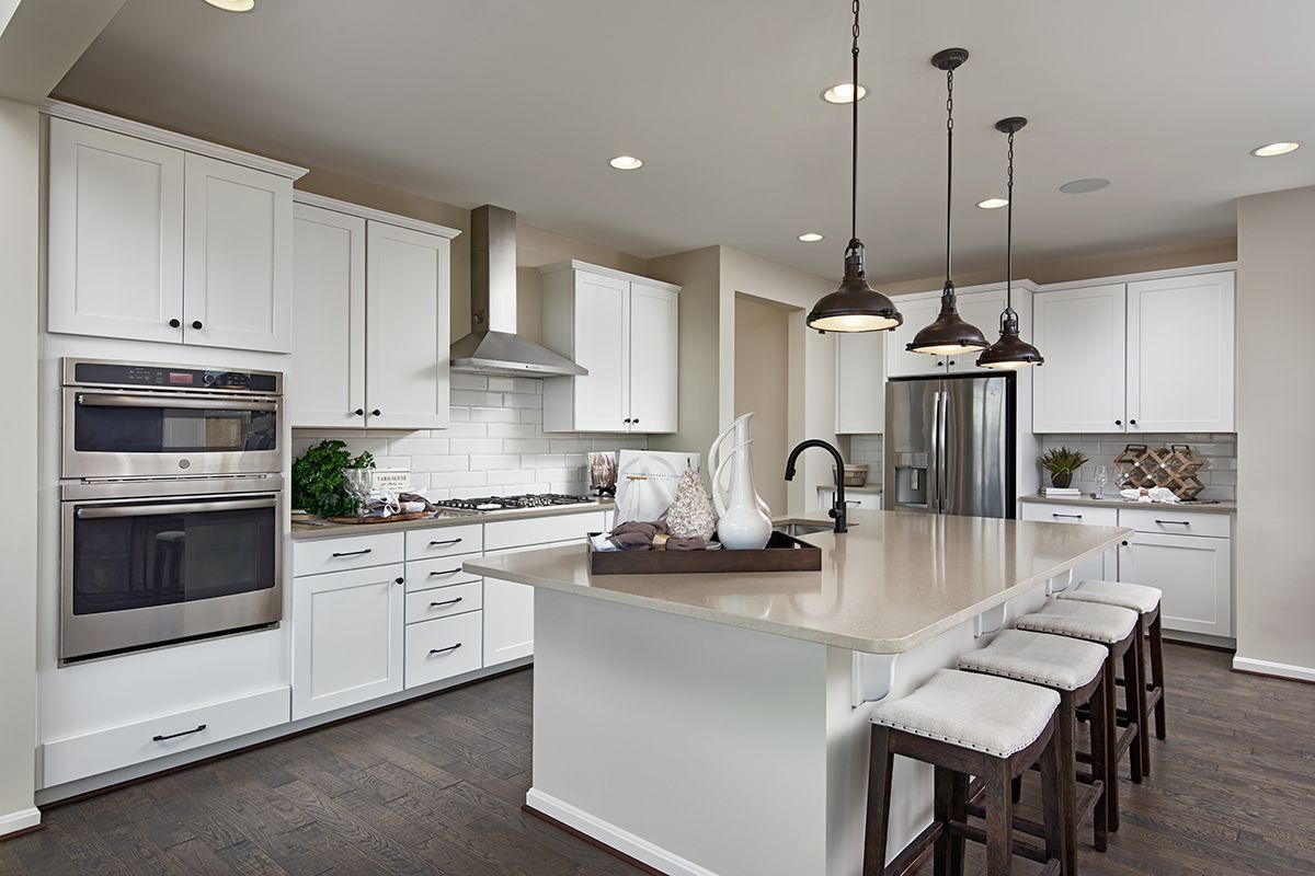 Bright, white kitchen with stainlesssteel hood & double