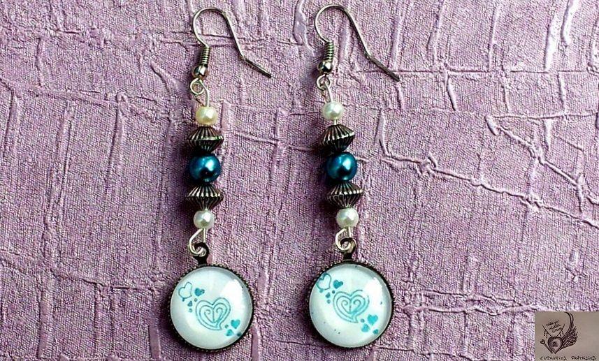* Boucles d'oreille cabochons en verre * stamping coeurs bleu turquoise *  Boucles d'oreille pendantes * vernies par mes soins en blanc * cabochons montés sur un support de couleur argenté. Assorties de deux perles en acrylique blanches, d'une perle en acrylique bleue turquoise et de deux perles en polyester.  Dimensions approximatives : cabochons ronds d'un diamètre de 16 mm longueur : 7 cm  Prix : 9,20 euros A retrouver sur la boutique * a little market *