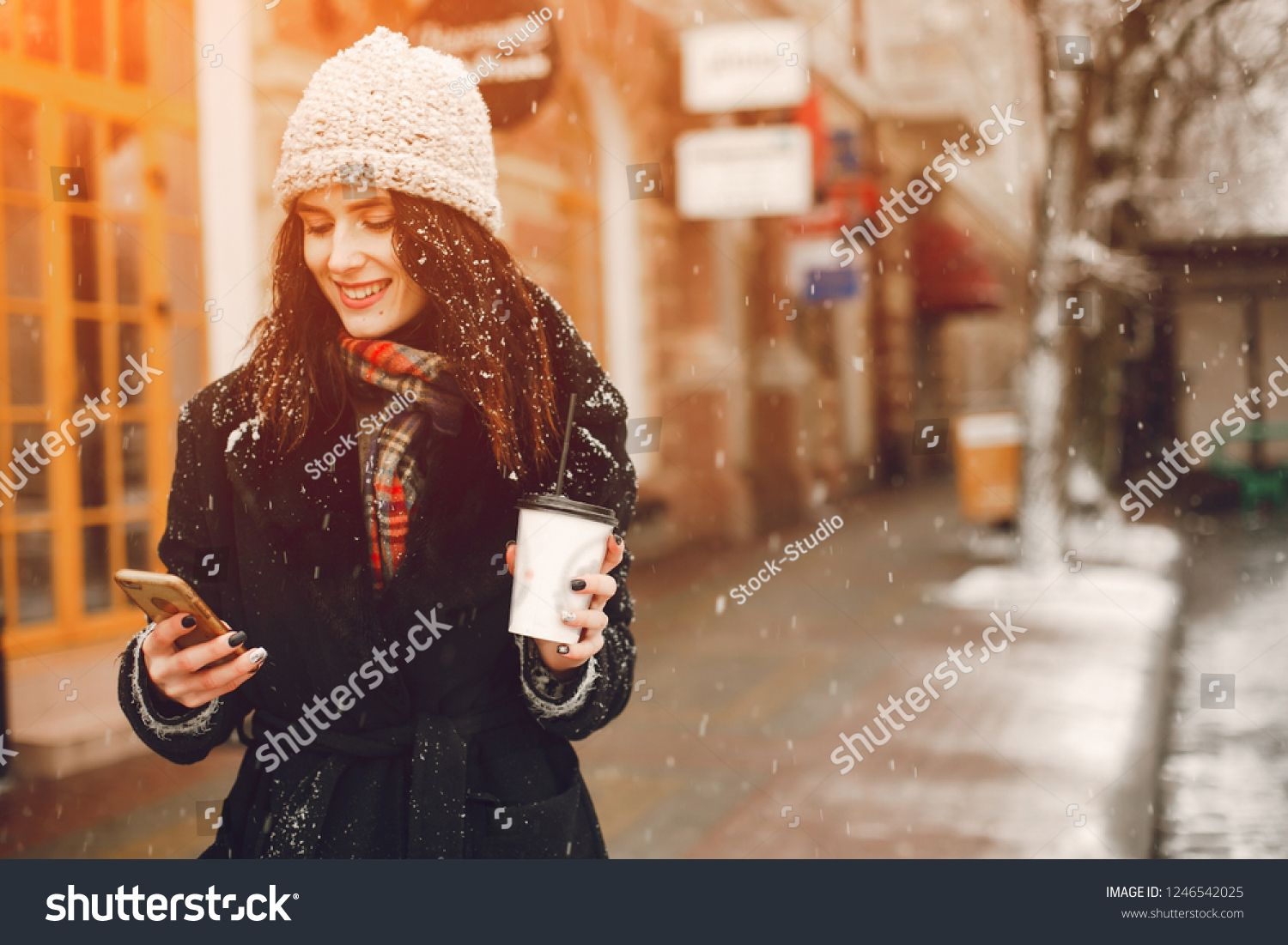 Young And Stylish Girl In Black Coat And White Hat Drinking Coffee