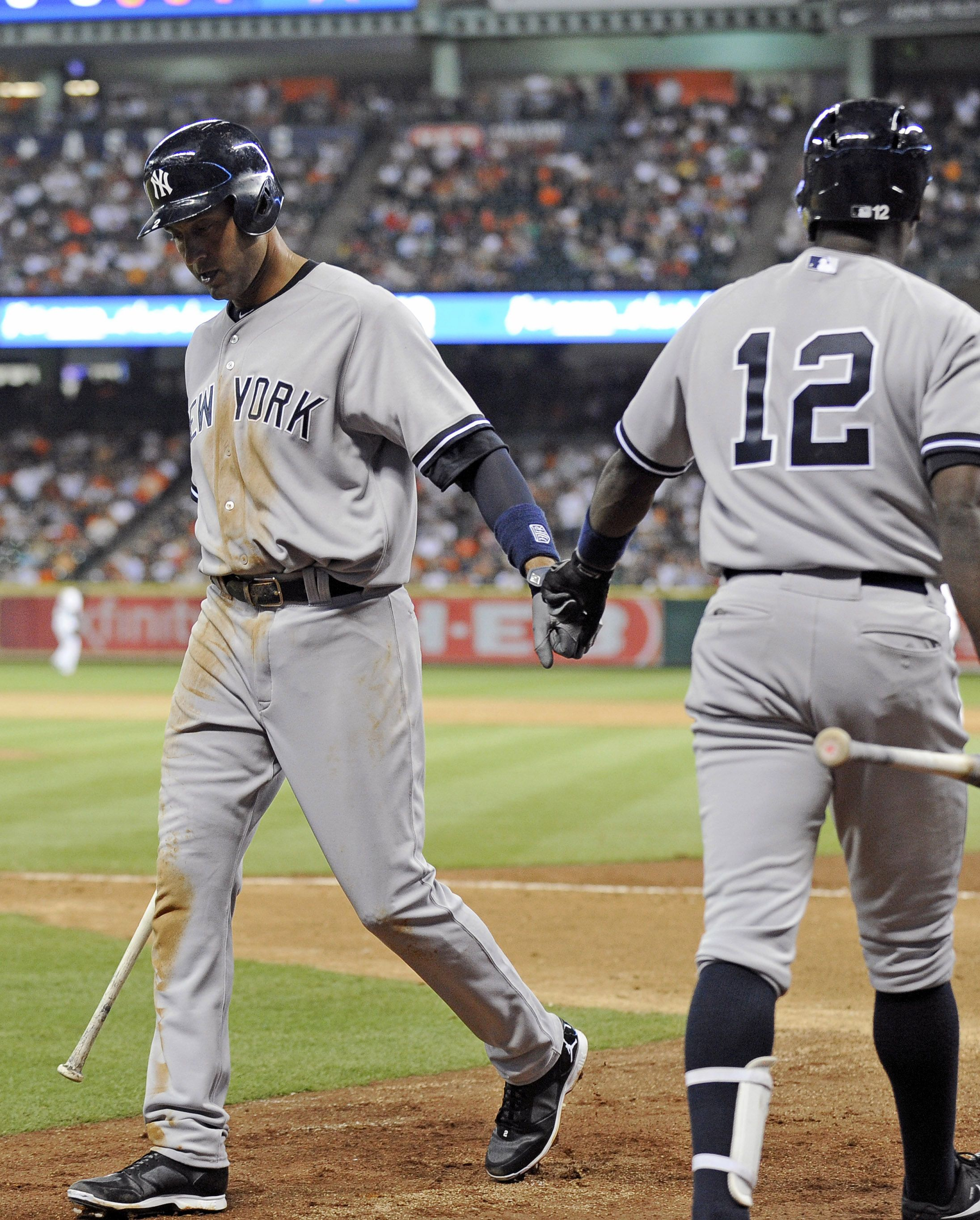 New York Yankees' Derek Jeter, left, is congratulated by Alfonso Soriano (12) after scoring on a Mark Teixeira single against the Houston Astros in the eighth inning of a baseball game on opening day for the teams, Tuesday, April 1, 2014, in Houston. (AP Photo/Pat Sullivan)