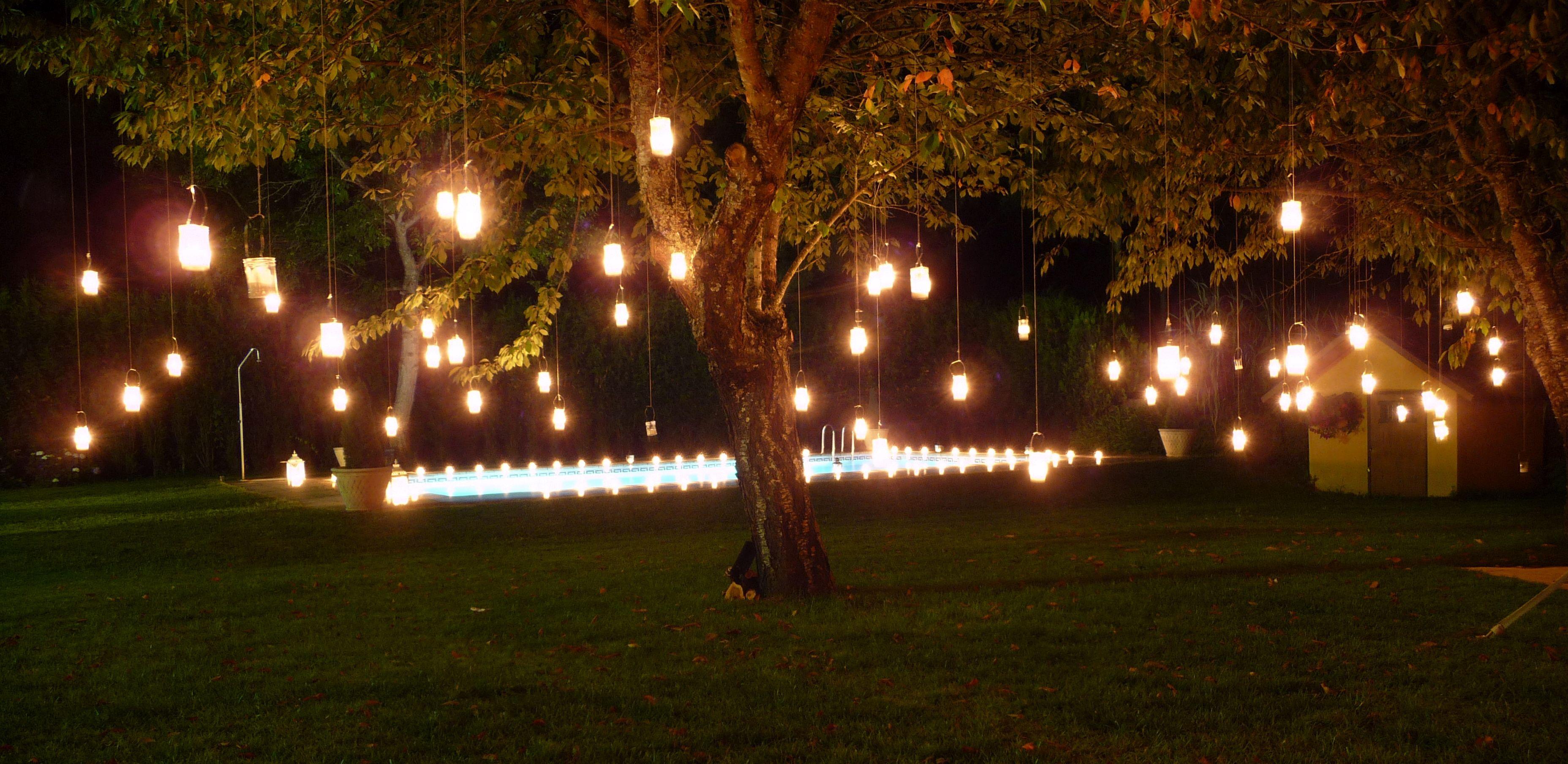 Iluminaci n nocturna con velas colgadas en los cerezos del for Luces colgantes para jardin