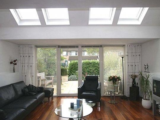 een uitbouw van de woonkamer met dakvensters en openslaande deuren ...