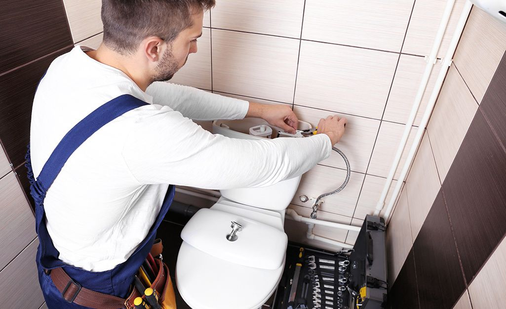 A man fixing the inside of a toilet tank. in 2020 | Toilet ...